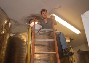 Tenuta Montiani winemaker sitting on a tank during winemaking process