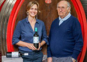 Tenuta di Tavignano winery owners holding bottle in Italy