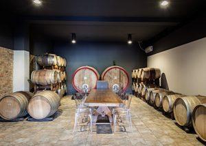 Tenuta Garetto wine tasting table inside cellar from huge barrels