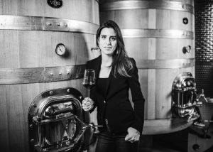 Tenuta Santi Giacomo e Filippo winery owner stands inside building with glass of wine