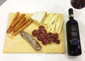 Varied Italian food and bottle of wine in Bogge wine before tasting.