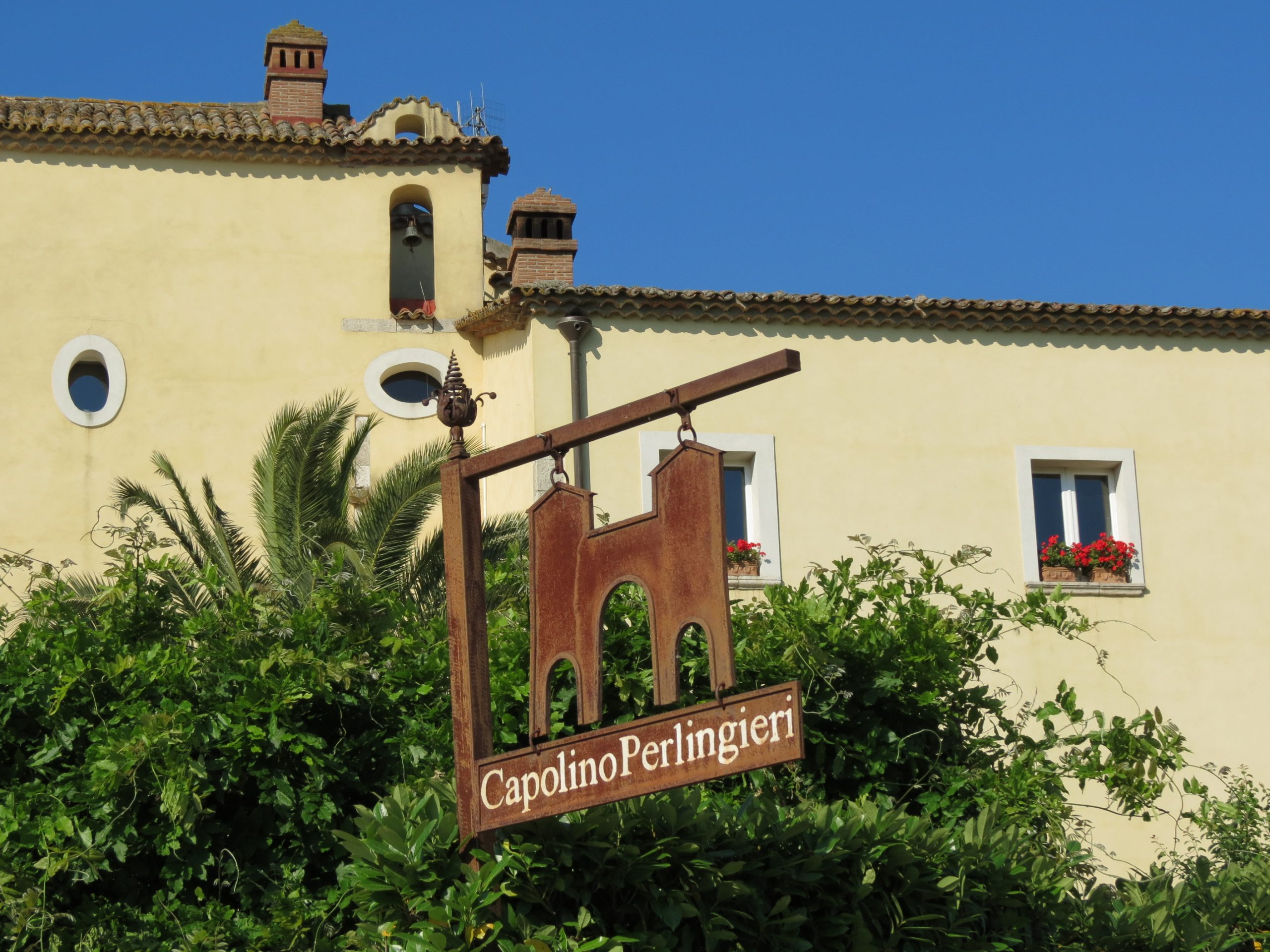 Capolino Perlingieri wooden signboard on the background of a beautiful mansion.
