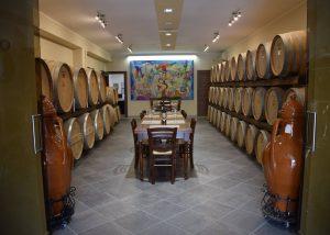 Wine cellar with barrels and artwork and tasting tables in Feudi di Guagnano.