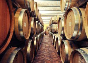 between rows of barrels inside Tenuta Il Falchetto winery cellar