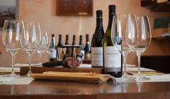 Wine bottles, glasses and salami prepared for tasting at Oscar Bosio.
