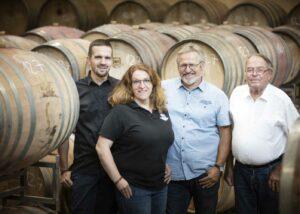 bergdolt-reif & nett winemakers team near wooden barrels in the wine cellar