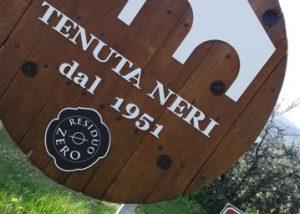 modern logo at Tenuta Neri Giovanni e Valeria near winery building