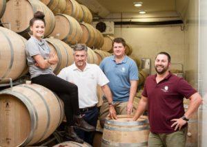 constantia glen winemakers near wooden barrels in the wine cellar