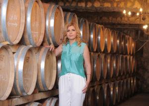 domeniile sahateni winemaker near wooden barrels for wine aging inside cellar