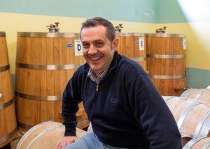 joyful winemaker in the modern cellar of the poderi vaiot winery.