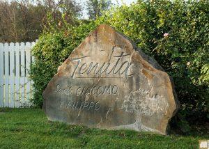 stone with logo of Tenuta Santi Giacomo e Filippo winery near building