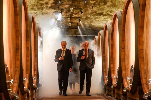 juliusspital winemakers near large wooden barrels in the wine cellar