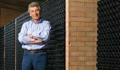 owner of the winery Domenico Clerico against wine bottles on racks.
