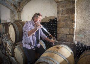 renčel wines winemaker inspecting wine from wooden barrel