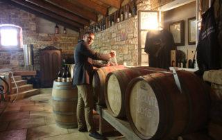 stancija collis winemaker in the wine cellar near barrels for wine aging