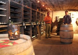 stettler-söhne visitors near wooden barrels in wine cellar in germany