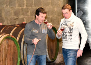 weingut familie rauen two visitors tasting wines in the cellar near barrels
