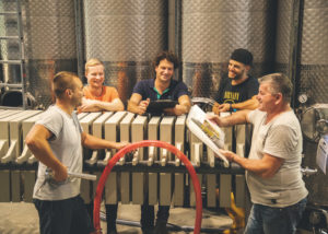 weingut trenz team of winemakers near steel tanks inside laboratory