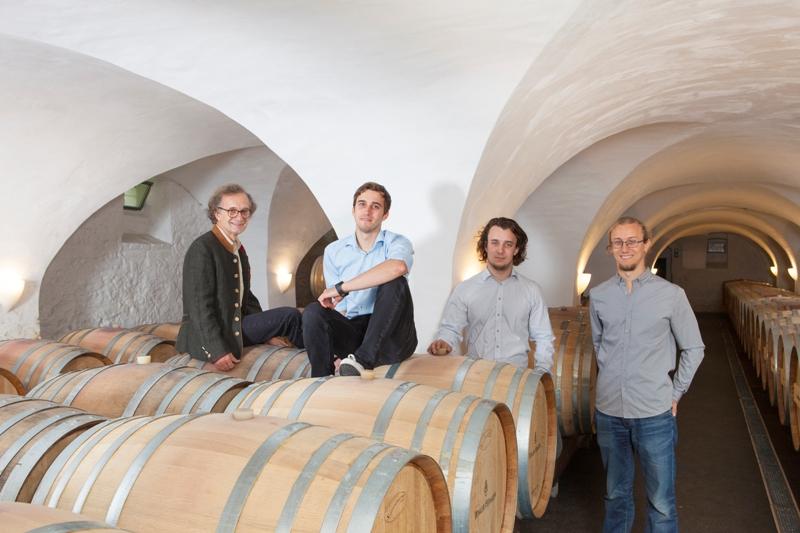 winkler-hermaden four winemakers in the wine cellar near wooden barrels