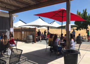 Tasting area outside the building of 3 steves winery with tables and chairs