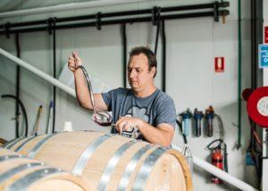 The winemaker of De Iuliis Wines tasting red wine from the barrel