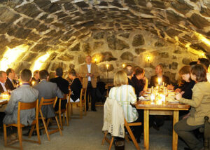 People enjoing their wine in the underground cellar at Blaxsta wines