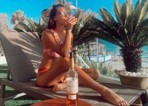 A woman in swimsuit tasting wine at Bodegas javier san pedro ortega winery near pool
