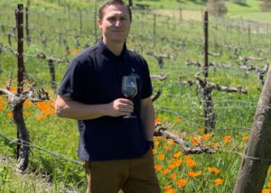 Owner of Clos lachance wines tasting wine in the vineyard