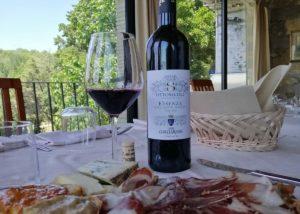 A bottle of the wine and food on the white table at CONTE GUICCIARDINI di Ferdinando Guicciardini - CASTELLO DI POPPIANO winery