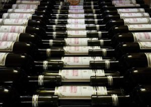 Bottles of wine by Domaine de maison blanche winery arranged in several rows.