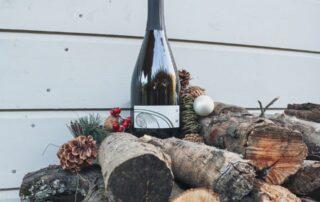 A bottle of wine by Domaine la colombe winery on wooden logs.