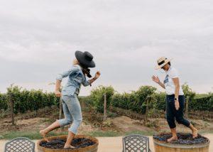 Two woman having fun in the vineyard of Et Cetera winery