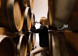 Owner of Le belle rebelle winery tasting wine in cellar beside stack of barrels