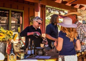 A man pouring wine by old creek ranch winery for a customer
