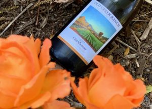 Bottle of wine by old creek ranch winery on ground with some orange flowers.