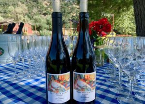 Two bottles of wine by old creek ranch winery on a table with several wine glasses