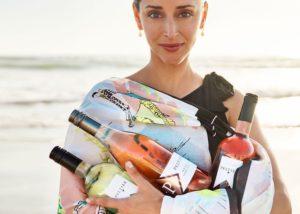 A woman holding three bottles of wine by Peltier winery