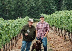 Owners of Phelps creek vineyards standing on passage between row of vines