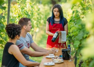 A couple enjoing wines near the vineyard of Schuchmann wines cateau, villas & spa and a lady serving wine
