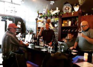 Three men enjoying their wines in the tasting room of Tero estates winery