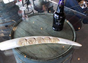 A bottle of wine by Turtle rock ridge on a wooden barrel with an art piece