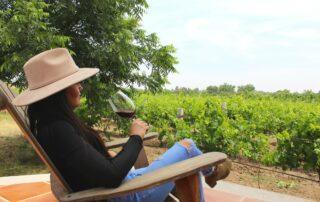 Woman tasting wine in the vineyard at Viña Las Cruces winery