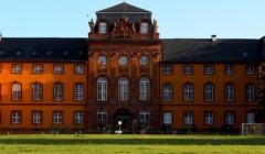 The main building of Weingut Fürst Löwenstein winery.with open grassland at front.