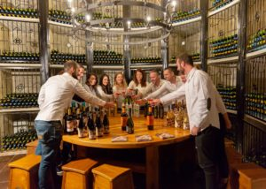 Group of people raising their wine glasses while tasting varities of wines at Bodegas Francisco Gomez tasting room.