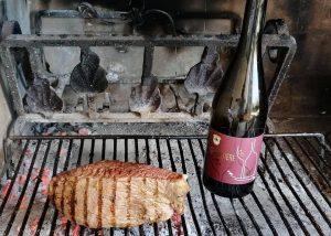 A Bottle Of Wine By Cantina Tamburino Sardo Di Fasoli Adriano & Figli Winery On Grill Along With A Steak
