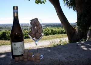 a bottle of wine by cantina tamburino sardo di fasoli adriano & figli along with a wine glass full of corks