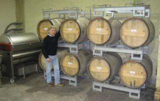 Hugo standing beside stacked barrels of wine in cellar at Court Garden Ltd.