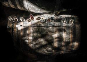 gutierrez colosia wine glasses on wooden barrel inside cellar