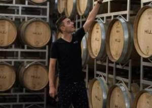 owner testing wines in the cellar of leo hillinger