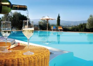 A Man Pouring Wine Into A Glass Of Wine Beside Pool At Mormoraia Winery